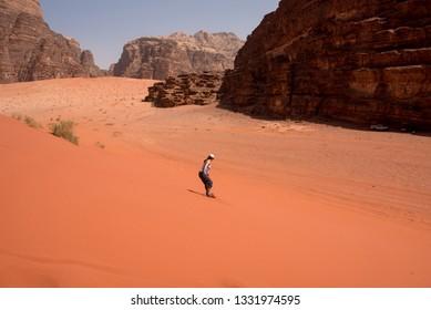 WADI RUM, JORDAN - MAY 18, 2018: Girl sandboarding on the red sand dunes of the desert