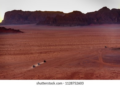 Wadi Rum, Jordan - November 26 2017: Caravan of off-road vehicles drive across the desert leaving behind dust trail at sunset. Landscape photography.