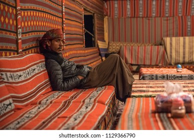 Wadi Rum, Jordan - November 26 2017: Bedouin man with turban inside a tent with colorful fabrics, traditional accommodation for tourists in the desert