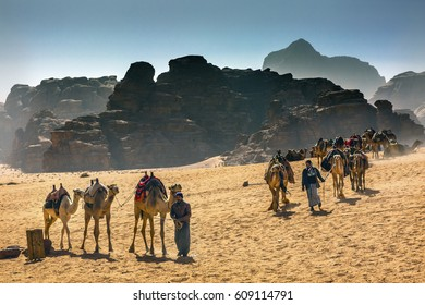 WADI RUM, JORDAN - NOVEMBER 26, 2016 Arab Bedouin Guides Camels Rock Formations Yellow Sand Camel Wadi Rum Valley of the Moon Jordan.  lace where TE Lawrence of Arabia in the early 1900s