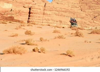 WADI RUM, JORDAN - OCTOBER 26, 2018: Bedouin's car jeeps and tourists in it in Wadi Rum desert in Jordan