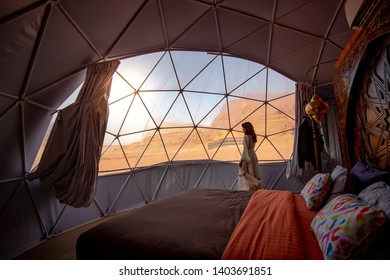 WADI RUM, JORDAN - OCTOBER 26, 2018 : Asian tourist woman in white dress in dome tent looking outside at Wadi Rum desert, famous natural attraction in Jordan. Travel Middle east concept