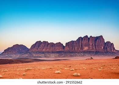 Wadi Rum in Jordan at twilight hour. Wadi Rum is known as The Valley of the Moon and has led to its designation as a UNESCO World Heritage Site.