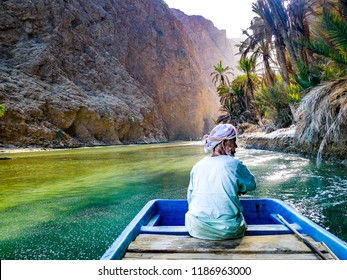 Wadi Shab, Oman - Jan 2012: An old Omani man steers a boat across the shallow green water at the entrance to Wadi Shab, a beautiful scenic canyon near Muscat in Oman