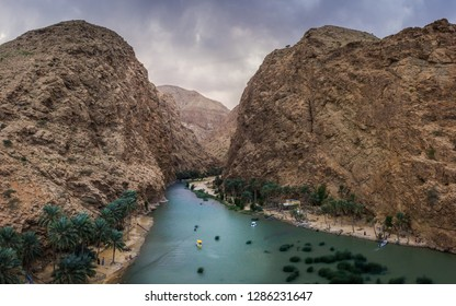 Wadi Shab, Oman. A view of a valley, canyon or wadi, with a water stream between large mountains and clouds and palm trees