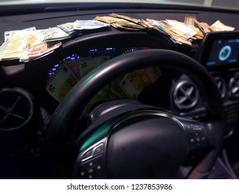 Wads of money on the dashboard of a luxurious car. Large amount of euros scattered. Succeed. Rich businessman.