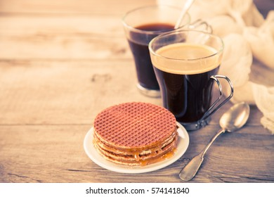 Wafers with caramel and coffee on a table. Selective focus. Copy space. The image is tinted