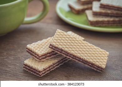 Wafers with chocolate on wooden table and coffee cup
