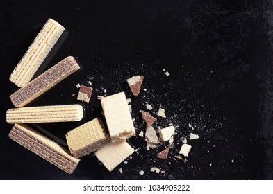 Wafers with chocolate and vanilla whole and crumbs on old black metal background, top view