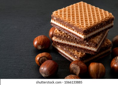 Wafers, cookies and sweets concept with hazelnut, chocolate and vanilla filled wafer stack with raw hazelnuts still in shell scatered around on a dark background