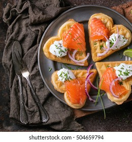 Wafers as heart shape with salted salmon, red onion, chive, lime and ricotta cheese on metal plate with vintage cutlery and sackcloth rag over dark rusty metal background. Top view.  Square image