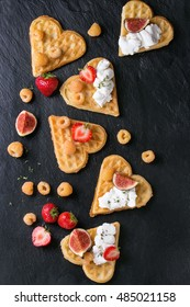 Wafers as heart shape with yellow raspberries, strawberries, sliced figs and ricotta cheese over black stone slate background. Top view with space for text