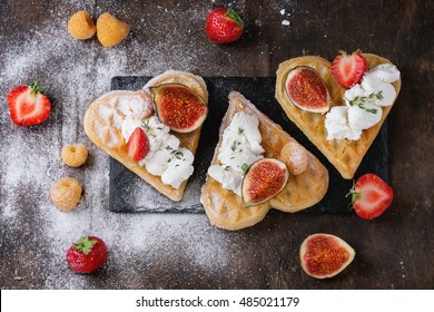 Wafers as heart shape with yellow raspberries, strawberries, sliced figs, ricotta cheese and sugar powder on black slate board over dark wooden background. Top view with space for text