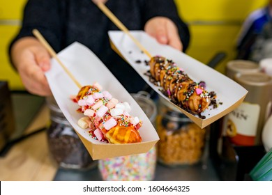 Waffel on a stick served from the hand at a foodtruck festival