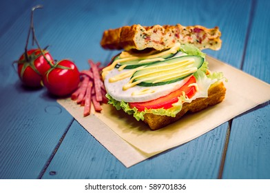 waffle Burger with egg, cucumbers and tomatoes on blue boards