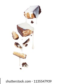 Waffle chocolate bar is poured over condensed milk, isolated on white background