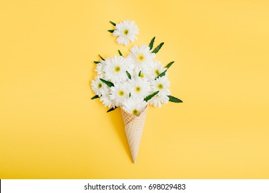 Waffle cone with chamomile flower bouquet on yellow background. Flat lay, top view floral background.
