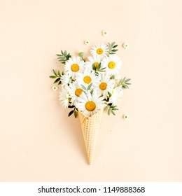Waffle cone with chamomile flower, leaves on beige background. Flat lay, top view floral background.