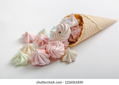 waffle cone with colored meringues on a white background