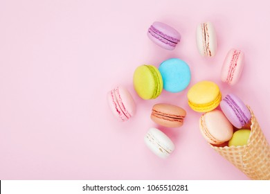 Waffle cone with colorful macaron or macaroon on pink pastel background top view. Flat lay composition.