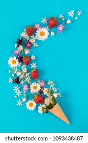 Waffle cone with fresh strawberries and flowers blossom  bouquets on blue surface. Flat lay, top view sweet food floral background.