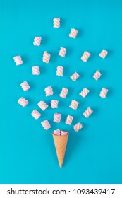 Waffle cone with marshmallow bouquet on blue surface. Flat lay, top view sweet food background.