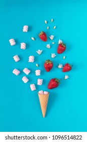 Waffle cone with marshmallows, fresh strawberries and flowers jasmine blossom bouquets on blue surface. Flat lay, top view sweet food floral background.