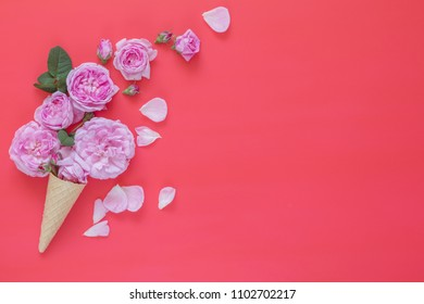 Waffle cone with pink roses flower bouquet on pink background. Flat lay, top view floral background