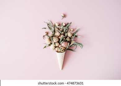 waffle cone with roses bouquet on pink background, flat lay, top view