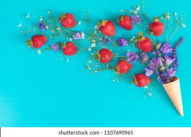 Waffle cone with wild strawberry and blue bells and white flowers blossom bouquets on blue surface. Flat lay, top view sweet food floral background.