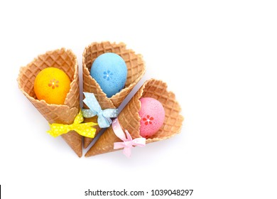 Waffle Cones with Easter eggs on white background. Space for text. Top view.