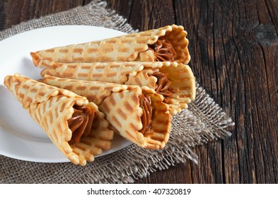 Waffle cones with sweet boiled condensed milk in plate on dark wooden table