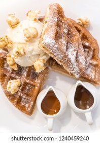 Waffle dressed with pop corn, ice cream and chocolate and caramel sauces