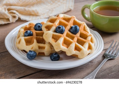 Waffle with fresh blueberry on plate and cup of tea