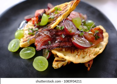 Waffle gourmet breakfast dish on a black plate with bacon and grapes and a beautiful decoration