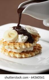 Waffle with Greek yogurt and banana under chocolate sauce closeup