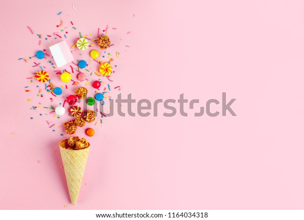 Waffle horn with colored candy, sweets, marshmallow, caramel popcorn, sweet powder on a pink background. Top view, sweets and candy concept. Copy space