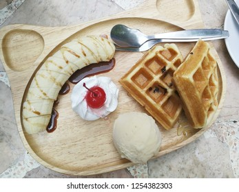 Waffle with ice cream and banana on the wooden plate