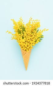 Waffle ice cream cone with mimosa flowers on a blue background. Spring concept. Copy space, top view