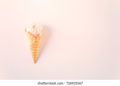 Waffle ice cream cones with scoops of ice cream on a pink background.