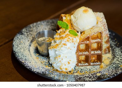 waffle with ice cream on wooden table. Dessert