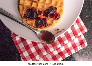Waffle on a plate over a checkered napkin. Top view closeup