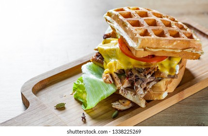 Waffle sandwich with meat, cheese, sauce and vegetables on wooden table background