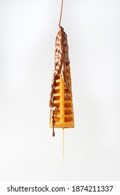 Waffle stick chocolate topping, tradicional flavor, dropping halzenut chocolate from top, white background