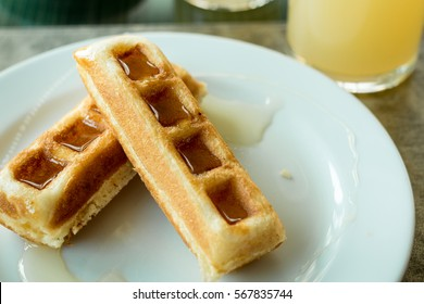 Waffle stick with maple syrup, waffles with syrup on white plate
