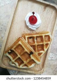 Waffle with whipping cream on the wooden plate
