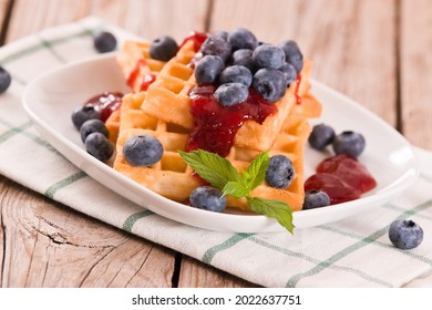 Waffles with blueberries and jam on white dish.