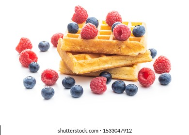 Waffles with blueberries and raspberries isolated on white background.