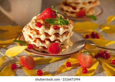 Waffles for breakfast, decorated with autumn leaves, Viennese waffles with berries. Waffles with strawberries