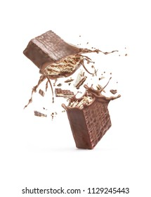 Waffles broken in half, with a chocolate splash isolated against a white background